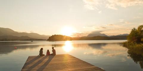 Familie sitzt auf Steg am See bei Abendstimmung