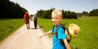 Familie wandert mit Sohn auf einem Landweg im Sommer