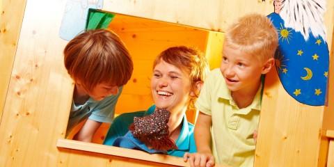 Kinderbetreuerin spielt mit zwei Kindern