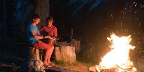 Zwei Jugendliche sitzen am Lagerfeuer und spielen Gitarre