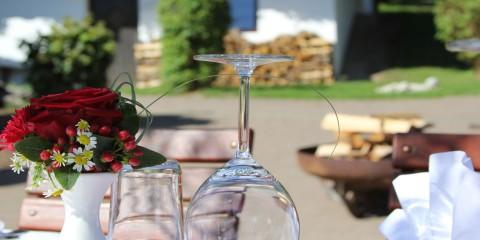 Umgedrehtes Glas und ein Blumenstrauß auf einem gedeckten Tisch