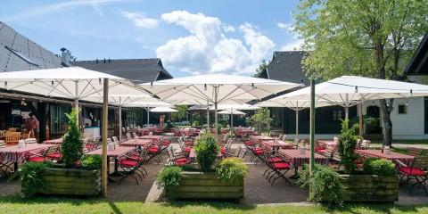 Gedeckte Tische mit Sonnenschirmen auf einer Gartenterrasse